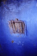 Wattle and daub wall: blue daub wall with rectangular hole in the centre through which the woven wattle framework is visible.